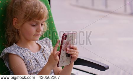 Portrait Of Attractive Smiling Child Girl In City Train Using Smartphone Chatting With Friends. Fema