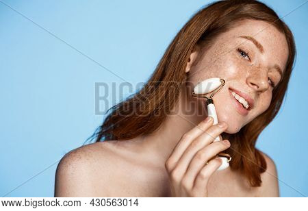 Beautiful Naked Redhead Woman Massaging Face With Jade Roller Isolated On Blue. Young Woman Using Gu