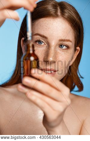 Beauty Face. Woman Applying Essential Oil On Facial Skin And Looking Away. Beautiful Model Moisturiz