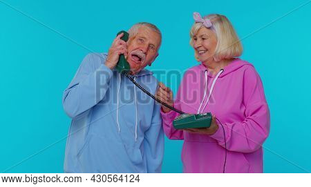 Crazy Senior Old Gray-haired Grandfather Grandmother Talking On Wired Vintage Telephone Of 80s, Fool