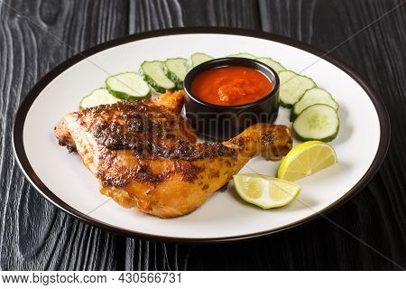 Tasty Ayam Bakar Hot Grilled Chicken Served With Cucumber, Lime And Sauce Closeup In The Plate On Th