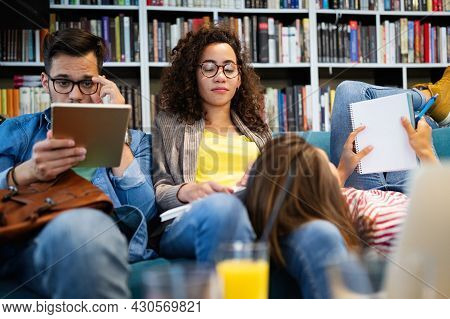 College, Study, University And Education Concept. Group Of Tired Students Learning In Library