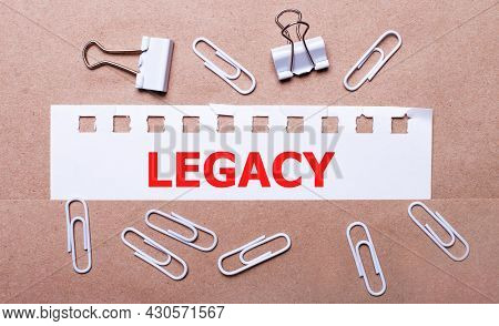On A Brown Background, White Paper Clips And A Torn Strip Of White Paper With The Text Legacy