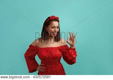 Pleased Smiling European Woman, Brunette In Red Dress With Bare Shoulders Wearing Hair Band Makes Ok