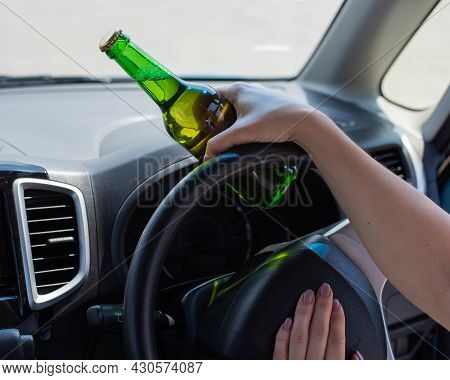 A Faceless Woman Is Drinking A Bottle Of Beer While Driving A Car. Breaking The Law And Drinking Alc