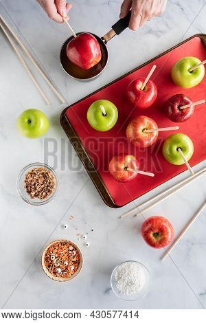 Top Down View Of Hands Dipping An Apple Into Caramel Sauce Surrounded By Ingredients To Make Caramel