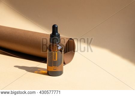Mock-up Of Glass Dropper Bottle On Background Of Rolled-up Brown Roll Of Paper. Object Casts Hard Sh