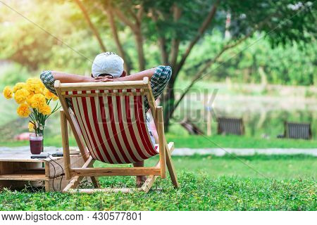 Back View Of Senior Man With White Hat Sitting On Garden Chair And By The Table In Garden. Summer Va