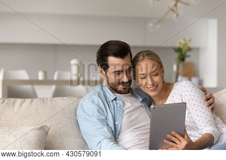 Happy Millennial Couple Relaxing At Home, Hugging On Couch