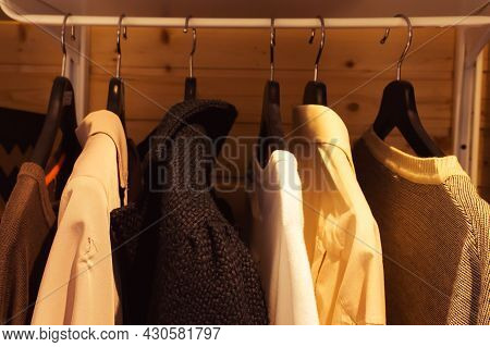 Warm Clothes On Hangers In The Closet. Sweatshirts Are Out Of Fashion In The Home Wardrobe