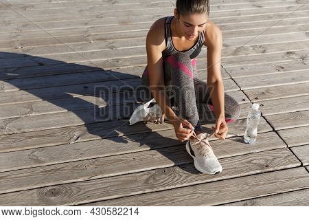 Outdoor Shot Of Young Fitness Woman Tying Shoelaces And Drinking Water During Workout