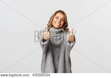Image Of Happy Beautiful Woman In Grey Sweater, Showing Thumbs-up And Smiling, Give Approval Or Agre