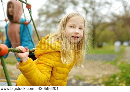 Two Adorable Young Girls Having Fun On A Playground Together In Beautiful Autumn Park. Cute Sisters
