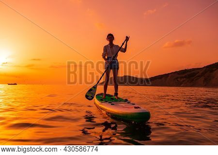 June 21, 2021. Anapa, Russia. Sporty Woman Paddle On Stand Up Paddle Board At Quiet Sea With Sunset
