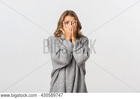 Image Of Scared Woman In Grey Sweater, Shut Her Eyes But Peeking Through Fingers At Something Scary,