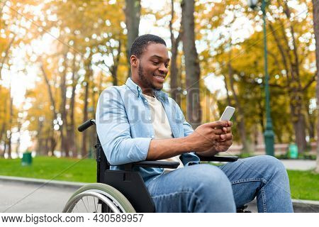 Cheery Disabled Black Guy In Wheelchair Using Mobile Phone, Checking Email Or Messages At Autumn Par