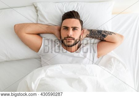 Depressed Young Man Unable To Sleep, Lying In Bed, Looking Up And Contemplating, Top View