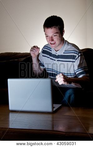 Young man excited by news on his computer