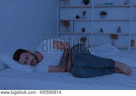 Sick Millennial Man Suffering Stomachache, Hugging Stomach While Lying In Bed At Night, Copy Space