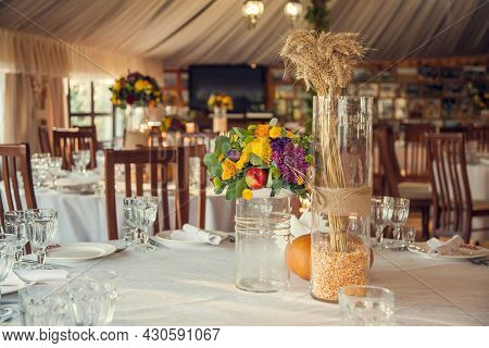 Banquet Hall Decorated With Flowers And Pumpkins In The Autumn Style. Festive Floristry And Decorati
