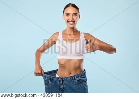 Woman Pulling Her Old Large Loose Jeans Showing Thumbs Up