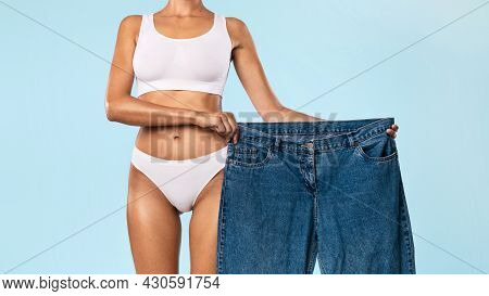 Fit Woman Holding Her Old Large Loose Jeans