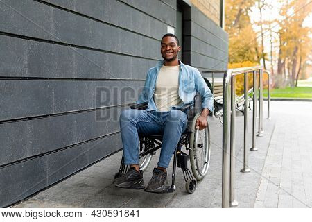 Handicapped Accessible City. Positive Impaired Afro Man In Wheelchair Leaving Building On Ramp Outdo