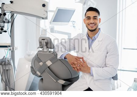 Dental Services. Portrait Of Professional Arab Stomatologist Doctor Posing At Workplace