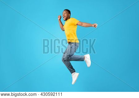 Joyful African Man Jumping And Shouting In Mid-air, Blue Background