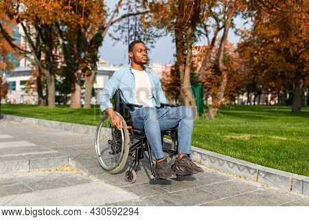 Paraplegic Black Guy In Wheelchair Going Down Ramp On On Walk At Park In Autumn, Using Impaired Frie