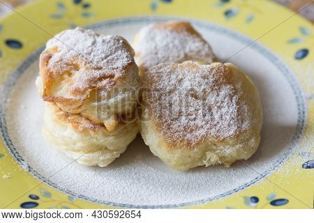Fried Fritters Sifted By Sugar Powder On Plate