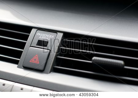 Close up detail of warning lights button and air vents inside a car