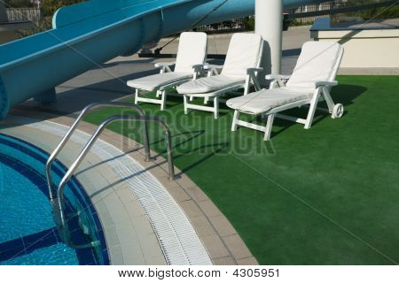 Chairs And Water Slide By Swimming Pool