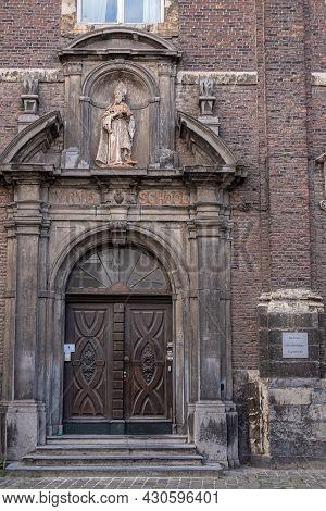 Gent, Flanders, Belgium - July 30, 2021: Brown Door In Dark Brick Entrance Wall Of Saint Stephens Ch
