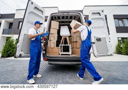 Two Removal Company Workers Are Loading Boxes And Furniture Into A Minibus.