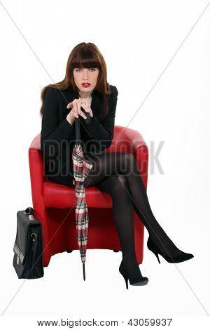 elegant business woman sitting in armchair
