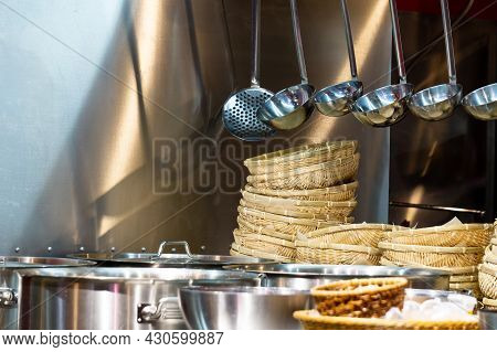 Kitchen Utensils In The Restaurant Kitchen. Soup Ladles Hang Over A Table With Pots And Wicker Plate