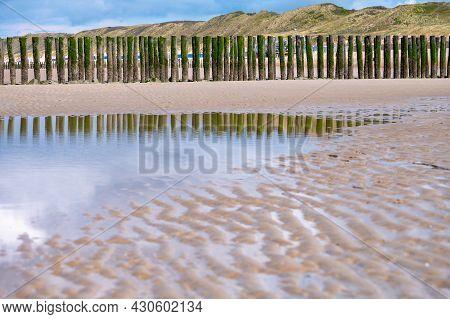 View On Wooden Poles At White Sandy North Sea Beach Near Zoutelande, Zeeland, Netherlands