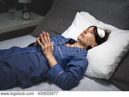 Pensive Mature Woman In Sleep Mask And Pajamas Lying On White Soft Linen And Keeping Eyes Open Durin