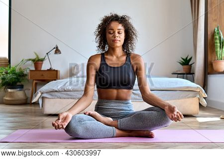 Young Calm Fit Healthy African American Woman Wearing Sportswear Sitting At Home In Bedroom Doing Yo