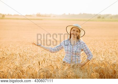 Happy Woman Farmer Looking At Camera With Hat In The Wheat Field With Outstretched Hand. Farmer Amer