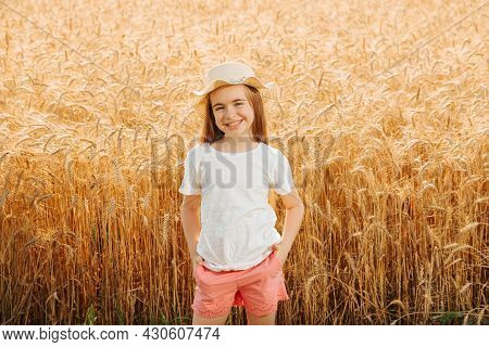 Little Girl Farmers Daughter In The Wheat Field Looking At Camera And Smiles Attractively. Adorable
