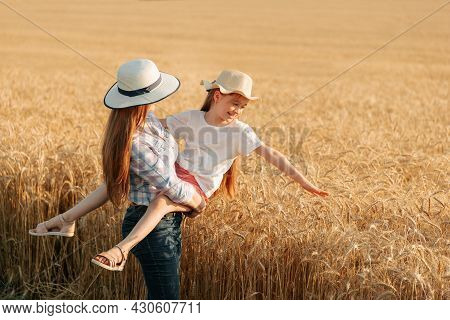 Woman Farmer With Hat Holds Her Child In Her Arms. Woman And Child In The Golden Wheat Field. Family