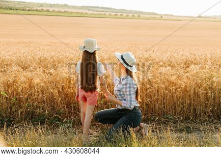 Rear View Of Mother And Daughter Pointing To Wheat Field. Mom And Her Kid Family Of Farmers With Hat