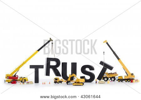 Building up trust concept: Black alphabetic letters forming the word trust being set up by group of construction machines, isolated on white background.