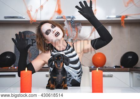 Woman Wearing Skeleton Costume With Disheveled Hairstyle And Themed Makeup Dances, Showing Gesture W