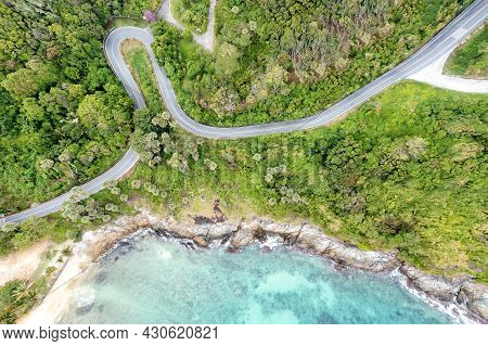 Aerial Drone Top Down View Of Waves Breaking In The Sand With Road And Forest. High Angle View Of Tr