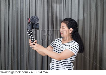 Young Woman Holding Mirrorless Camera With Gorilla Tripod, Looking At The Camera And Talking For Cre