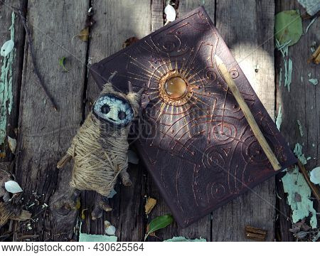 Magic Book With Decorated Cover And Voodoo Doll On Planks In The Garden Outside. Esoteric, Gothic An