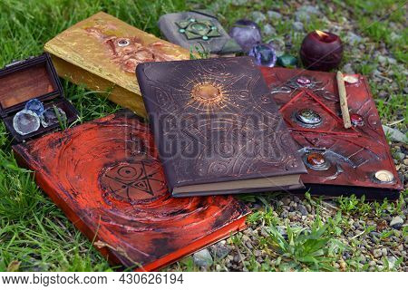 Pile Of Witch Grimoire Book Of Magic Spells And Burning Candle In The Garden. Esoteric, Gothic And O